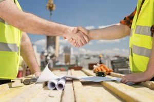 Construction workers shaking hands on construction